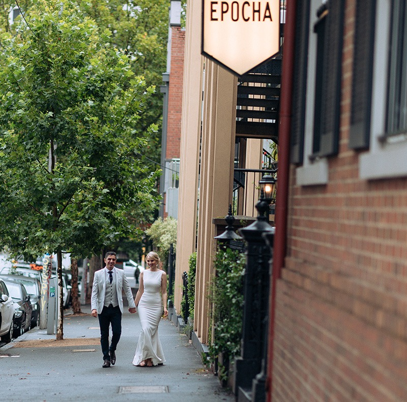 Bride & Groom walking towards Epocha restaurant