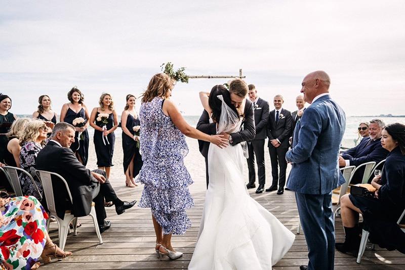 Bride and Groom embrace at Sandbar Beach Cafe wedding
